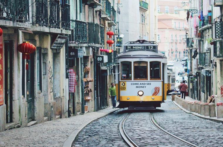 imagem empreender em Portugal: bonde amarelo em rua de paralelepípedos