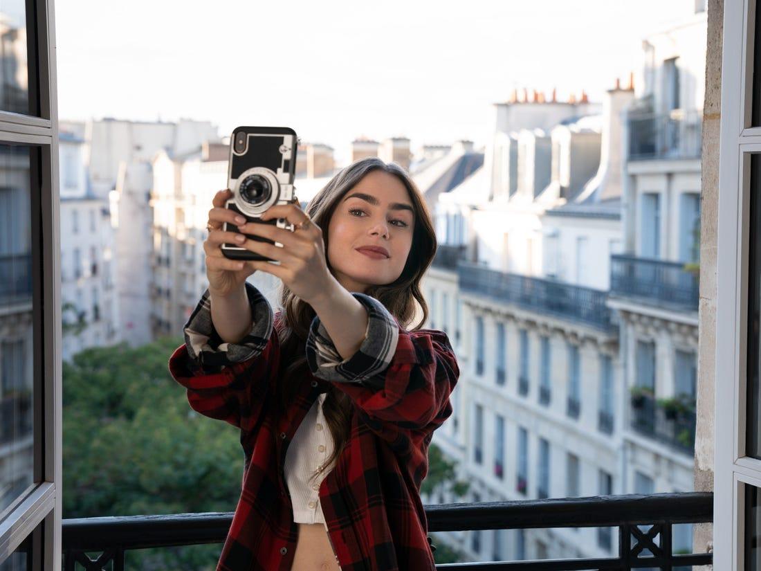 Emily tirando foto no novo apartamento
