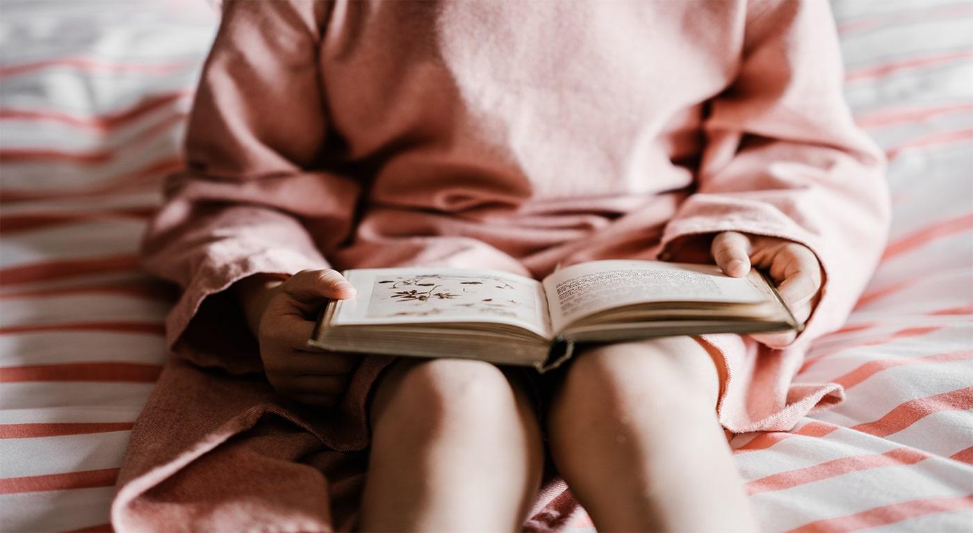 Foto de uma criança sentada na cama com um vestido rosa e comum livro aberto na mão.