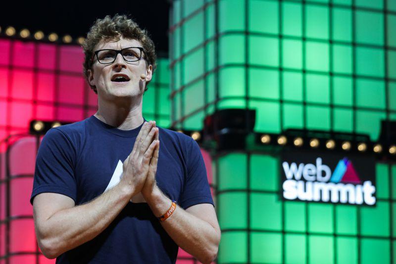 homem de blusa azul em frente a painel multicolorido da web summit